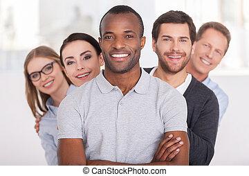 debout, regarder, garder, team., groupe, professionnels, bras, jeune, gai, confiant, derrière, appareil photo, quoique, africaine, traversé, homme souriant, lui, rang