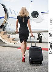 marche, femme, jet, bagage, privé, vers, vue postérieure